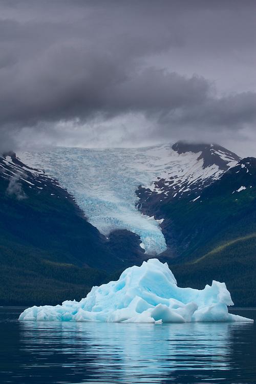 USA, Alaska, Tracy Arm - Fjords Terror Wilderness, Deep blue glacial iceberg floating in Holkham Bay beneath Sumdum Glacier on summer evening