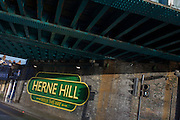 Old railway-style sign under railway bridge in Herne Hill, South London SE24. The mural is one of many in south London by the artist Lionel Stanhope.