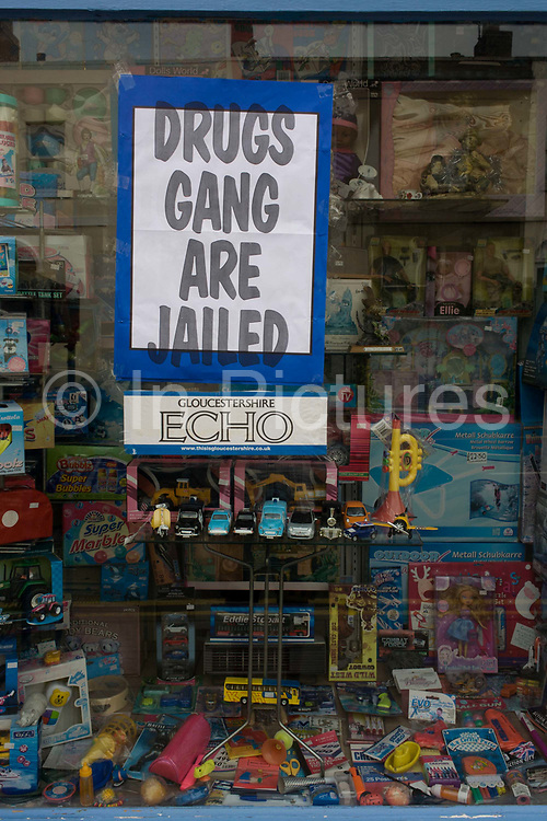 A local newspaper headline with news of a drugs gang jailing verdict, appears in a Cheltenham toyshop window, Gloucestershire, England. The Gloucestershire Echo's poster that occupies the centre of the glass tells locals that the notorious gang are now behind bars. In the background are the toys and games of childrens' innocence, a contrast to a real, violent world of drugs and crime.