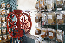 Red wheel from old manufacturing equipmenrt and display of chiles and spices at Pendery's World of Chiles & Spices retail store, Fort Worth, Texas USA.