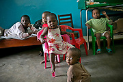 Orphans in Centre de la Mere et de l'Enfant rest in a room in Bangui. Most of the orphans here were left by their biological parents, and adopted to families overseas.