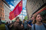 """01/05/2015 – Berlin, Germany: A man dressed as a Soviet soldierholding a flag of the USSR walks on the """"Myfest"""" street festival. """"Myfest"""" takes place in district SO 36, the traditional centre of riots that usually occur during May Day celebrations and it was organized to decreased the violence caused by Revolutionary May Day Demonstrations.  The radical left wing criticises such events claiming that it is pretended to pacify social conflicts and to ban radical demonstrations. The International Workers Day is a celebration of laborers and the working classes that is promoted by the international labor movement, anarchists, socialists, and communists and occurs every year on May Day. (Eduardo Leal)"""