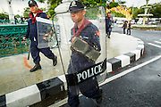 23 NOVEMBER 2012 - BANGKOK, THAILAND:  Thai riot police walk to their station near Government House in Bangkok Friday. Thai authorities have imposed the Internal Security Act (ISA), that enables police to call on the army if needed to keep order, and placed thousands of riot police in the streets around Government House in anticipation of a large anti-government protest Saturday. The group sponsoring the protest, Pitak Siam, said up to 500,000 people could turn out to protest against the government. They are protesting against corruption in the current government and the government's unwillingness to arrest or pursue fugitive former Prime Minister Thaksin Shinawatra, deposed in 2006 coup and later convicted on corruption charges. The current Thai Prime Minister is Yingluck Shinawatra, Thaksin's sister.      PHOTO BY JACK KURTZ