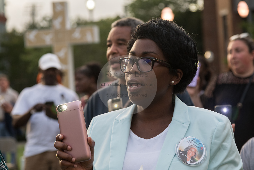 Denise Quarles, daughter of Myra Thompson killed in a mass shooting at the historic Mother Emanuel African Methodist Episcopal Church, holds up a flashlight during a candlelight vigil marking the 4th anniversary of the mass shooting June 19, 2019 in Charleston, South Carolina. Nine members of the historically black congregation were gunned down during bible study by a white supremacist on June 17, 2015.