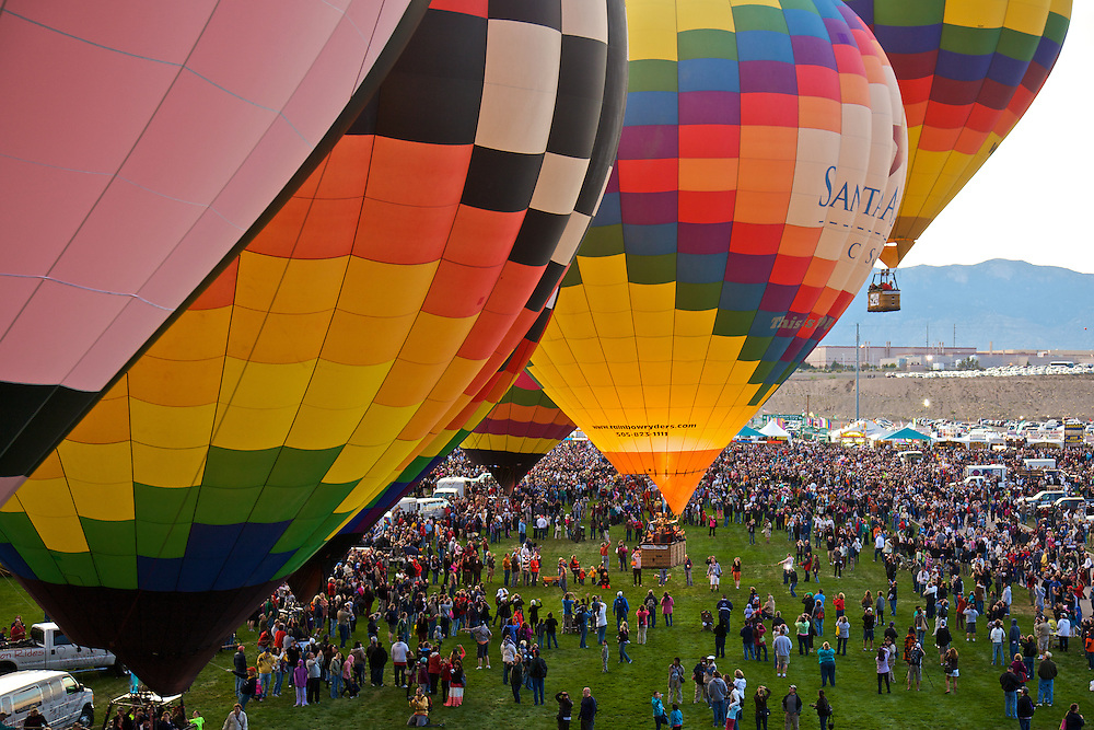 A row of colorful hot air balloons launches from the Albuquerque balloon field during its annual balloon fiesta