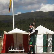 Highland Games, 3rd of August 2019, Newtonmore, Scotland, United Kingdom. A man plays his bag pipe as part of the best bag piper competition watched by two judges. The Highland Games is a traditional annual event where competitors compete as strong men, runners, dancers, pipers and at tug-of-war. The games go back centuries and are happening through-out the summer across Scotland. The games are both an important event locally and a global tourist attraction.