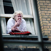 Lady leans out window cheeky smoke, Amsterdam, Netherlands (September 2006)