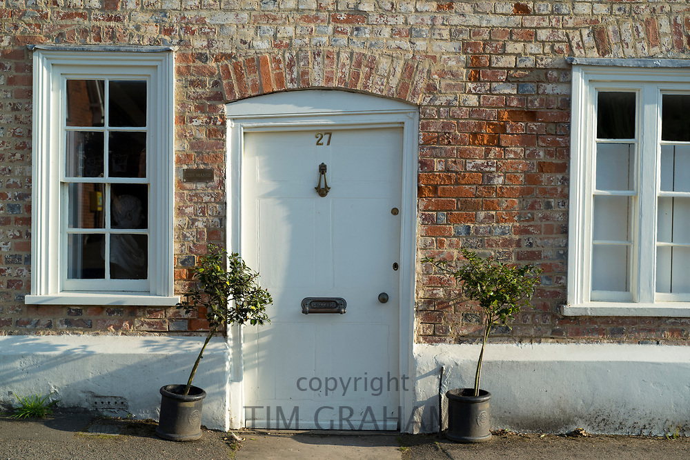 Quaint door and windows painted white of brick built typical English cottage with bay trees in Ramsbury, Wiltshire, UK
