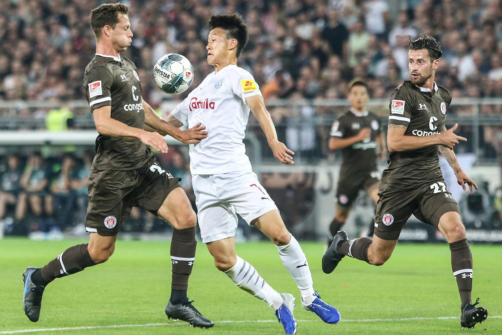 Fussball: 2. Bundesliga, FC St. Pauli - Holstein Kiel 2:1, Hamburg, 26.08.2019<br /> James Lawrence (Pauli, l.) - Jae Sung Lee (Kiel)<br /> © Torsten Helmke