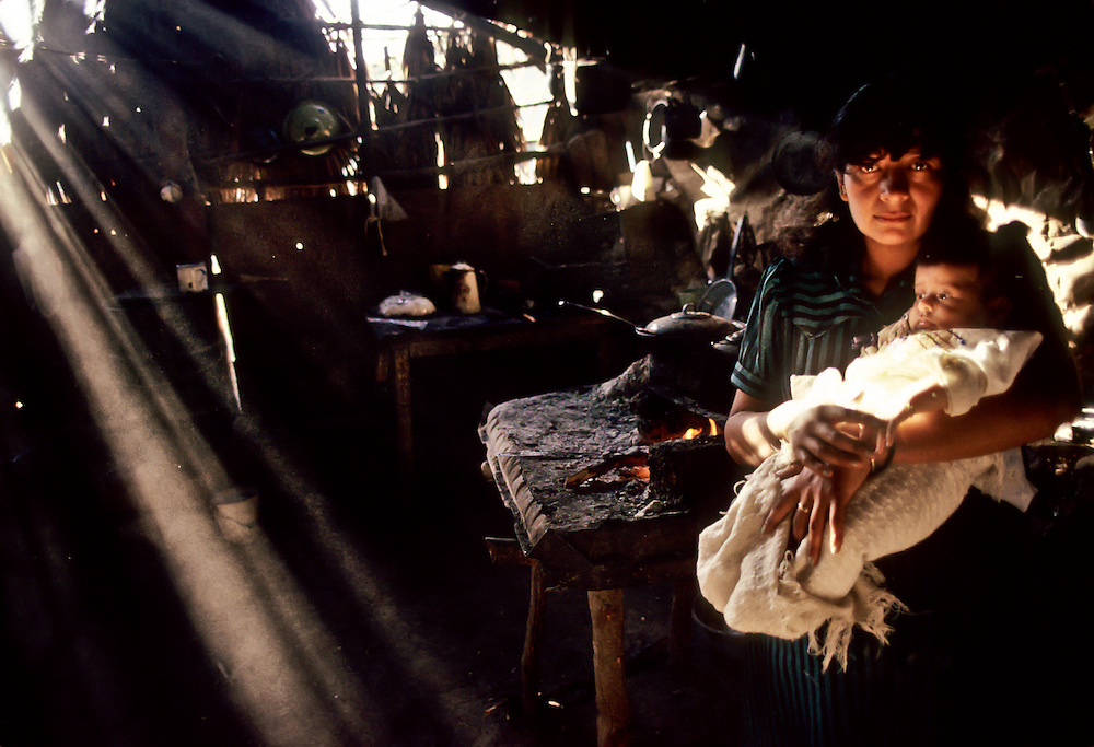 A woman and her infant child stand in their home, filled with smoke from cooking fires, in Baja California.