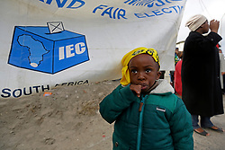 Wednesday 8th May 2019.<br /> Monwabisi Park, Harare,<br /> Khayelitsha, Cape Town, <br /> Western Cape, <br /> South Africa.<br /> <br /> SOUTH AFRICAN GENERAL ELECTIONS 2019!<br /> <br /> SOUTH AFRICAN PROVINCIAL AND NATIONAL ELECTIONS 2019! <br /> <br /> A young boy wears an ANC political party t-shirt as a bandana as he stands next to an IEC (Independent Electoral Commission) banner outside the voting station at Monwabisi Park, Harare in Khayelitsha near Cape Town, Western Cape, South Africa.<br /> <br /> Registered South African Voters head to the various IEC (Independent Electoral Commission) Voting Stations where they are registered to vote as they cast their votes and take part in voting and other activities on Voting Day 8th May 2019 during the South African General Elections 2019. Voters from across the nation stood in queue's along with many others to vote in the Provincial and National Elections being held in South Africa on Wednesday 8th May 2019.   <br />  <br /> Copyright © Mark Wessels. All Rights Reserved. No Usage Without Permission.<br /> <br /> PICTURE: MARK WESSELS. 08/05/2019.<br /> +27 (0)61 547 2729.<br /> mark@sevenbang.com<br /> studioseven@mweb.co.za<br /> www.markwesselsphoto.com