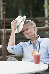 Man sitting table straw hat cocktail relaxing