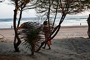 A woman walks at sunset on Parangtritis Beach. Special Region of Yogyakarta Province, Indonesia