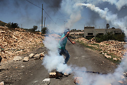 June 23, 2017 - Nablus, West Bank, Occupied Territories -  A Palestinian protester throws back a tear gas canister fired by Israeli soldiers during clashes after a protest against the expanding of Jewish settlements in Kufr Qadoom village near the West Bank city of Nablus. (Credit Image: © Zhaoyue/Xinhua via ZUMA Wire)