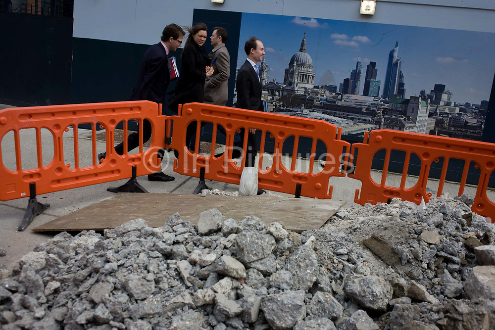 City workers walk past a pile of construction rubble near an skyline illustration of the City of London. The Londoners are having to detour around the fencing that is blocking the pavements, the site fences preventing them from straying into the area where rubble is being piled. The Cityscape in the background tells us about the UK's capital including the towering dome of St Paul's Cathedral and other financial institutions.