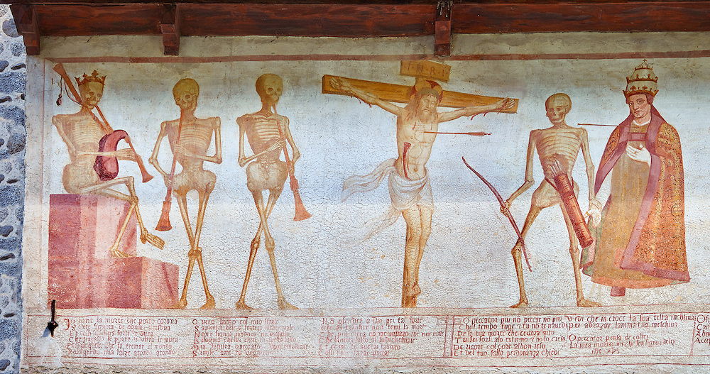 """Crucifiction fresco on the Church of San Vigilio in Pinzolo, part of its mural painting """"the Dance of Death"""" painted by Simone Baschenis of Averaria in1539, Pinzolo, Trentino, Italy.<br /> <br /> The mural continues for another 21 meters with a long procession with 40 figures.<br /> <br /> The Mural opens on its left with a skeleton on the throne, bearing a sceptre and the crown and playing a bagpipe. These skeletons are playing the music which is the backdrop to """"Dance of Death"""" ( Danza macabra ) and suggests that they are playing with our fate on earth.<br /> <br />  To the right of the skeletons playing music is a depiction of the crucification. Christ is depicted on the cross with an arrow in him that has been fired by a skeleton with a bow. This suggests that because Christ was a man he suffered the fate of death as we all will.<br /> After Christ is a Pope also pierced by a spear, as are all the human figures in the mural. ..<br /> <br /> Visit our MEDIEVAL ART PHOTO COLLECTIONS for more   photos  to download or buy as prints https://funkystock.photoshelter.com/gallery-collection/Medieval-Middle-Ages-Art-Artefacts-Antiquities-Pictures-Images-of/C0000YpKXiAHnG2k<br /> <br /> If you prefer to buy from our ALAMY PHOTO LIBRARY  Collection visit : https://www.alamy.com/portfolio/paul-williams-funkystock/san-vigilio-pinzolo-dance-of-death.html ."""