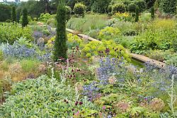 Narrow canal and mixed borders at Broughton Grange. Planting includes Eryngium x zabelii, Allium sphaerocephalon, Stachys byzantina and Taxus baccata 'Fastigiata'