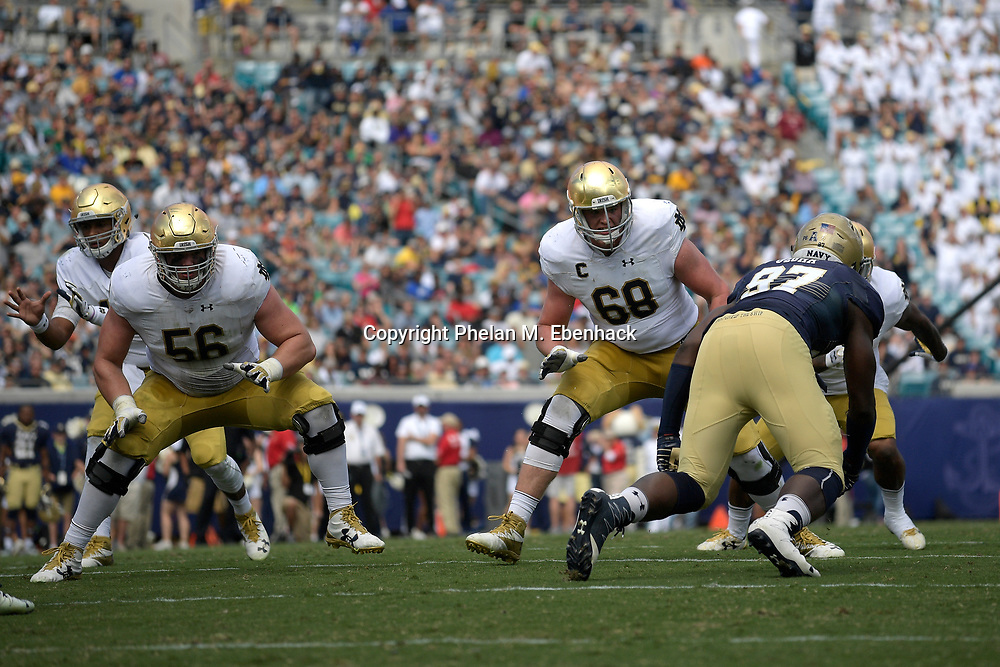 Notre Dame offensive lineman Quenton Nelson (56) and offensive lineman Mike McGlinchey (68) set up to block Navy defensive end Nnamdi Uzoma (97) during the second half of an NCAA college football game in Jacksonville, Fla., Saturday, Nov. 5, 2016. Navy won 28-27. (Photo by Phelan M. Ebenhack)