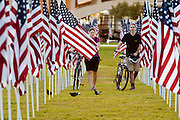 """10 SEPTEMBER 2011 - TEMPE, AZ:    JULIANNE ANDERSON, left, and MATTHEW BOWLES, both from Tempe, AZ, walk through the """"Healing Field"""" in Tempe, Saturday. The """"Healing Field,"""" a display of 2,996 flags, one for each person killed in the September 11 terrorists attacks on the World Trade Center in New York City and Washington DC, have become an annual tradition in Tempe. The event is sponsored by the National Exchange Club.      PHOTO BY JACK KURTZ"""