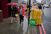 Commuters and upside down GO construction traffic sign in a busy London rush-hour street. Walking past a stack of worksite equipment, two women with red umbrella and raincoat maketheir way on a typical spring day on a central London street. The green sign stands upright near red lines denoting a Red Route, a main route in and out of the City, the capital's financial heart and oldest district founded by the Romans in AD43.
