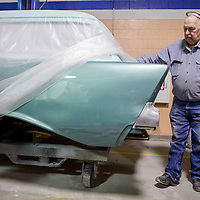 Instructor Floyd Clifford Burnham pulls back the cover on a 1957 Chevrolet wagon at the UNM-Gallup auto body shop Tuesday.