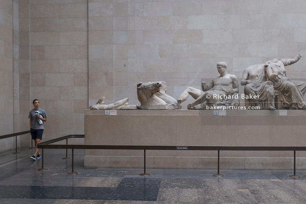 A visitor walks around the Parthenon (Elgin) Marbles in Room 18 of the British Museum, on 12th June 2018, in London, England.