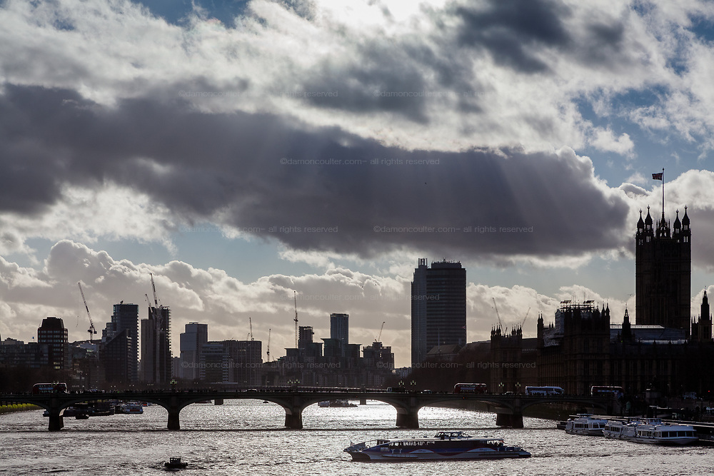 A tourist sightseeing boats crosses the River Thames under a moody sky with the palace of Westminster and more modern buildings in silhouette behind. London, UK. Friday January 5th 2018