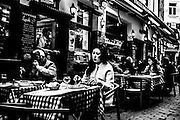 March 2015. Brussels. An asian girl is eating on a restaurant of touristic street near the Big square.