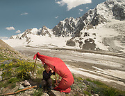 A child make a makeshift tent with sticks and red cloth during a trekking trip over a high pass in the mountains.