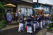 The Mikoshi is carried through the village of Kiso Mura as part of the Summer festival parade. Here been ovesrlloked by Kazufumi Okutani, 71 the senior Shinto priest of the village of Kiso Mura. For all the participants it's an all day sake drinking affair, stopping en route to soak up the alcohol with food as they sing along as part of the celebrations. The Mikoshi is also a portable Shinto shrine which on continuation of the ceremony is then carried by a large number of strong young men on their shoulders across the village for approximately 12 – 14 hours.