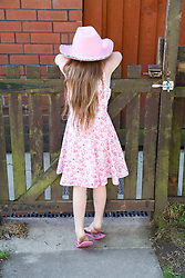 Little girl leaning over a garden gate,