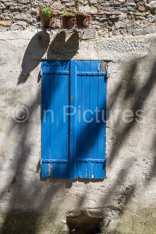 Closed blue shutters and shadows from pots and overhead trees of a village house, on 25th May, 2017, in Lagrasse, Languedoc-Rousillon, south of France. Lagrasse is listed as one of Frances most beautiful villages and lies on the famous Route 20 wine route in the Basses-Corbieres region dating to the 13th century.