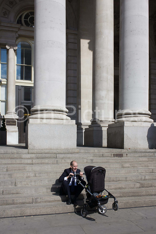 A businessman childminds in the City of London. With minutes to spare in warm sunshine, the man shows paternal instincts and sits at the bottom steps and tilts the unseen child seated safely in the family pushchair, pulling faces and keeping it entertained beneath the tall columns of this architecture in the Square Mile, the oldest and financial heart of the capital. The classic neo-Romanesque architecture of the Royal Exchange building has Doric and Ionic columns with their ornate stonework, designed by Sir William Tite in 1842-1844 and opened in 1844 by Queen Victoria). It's the third building of the kind erected on the same site. The first Exchange erected in 1564-70 by sir Thomas Gresham but was destroyed in the great fire of 1666. It's successor, by Jarman, was also burned down in 1838. The present building is grade 1 listed and cost about £150,000.