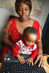 Mother on computer with daughter on the desk.