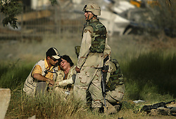 An injured Iraqi woman cries outside the UN base at the Canal Hotel where a cement truck packed with explosives detonated outside the offices killing 20 people and devastating the facility in Baghdad, Iraq on Aug. 19, 2003. This was an unprecedented suicide attack against the world body with at least 100 people wounded.