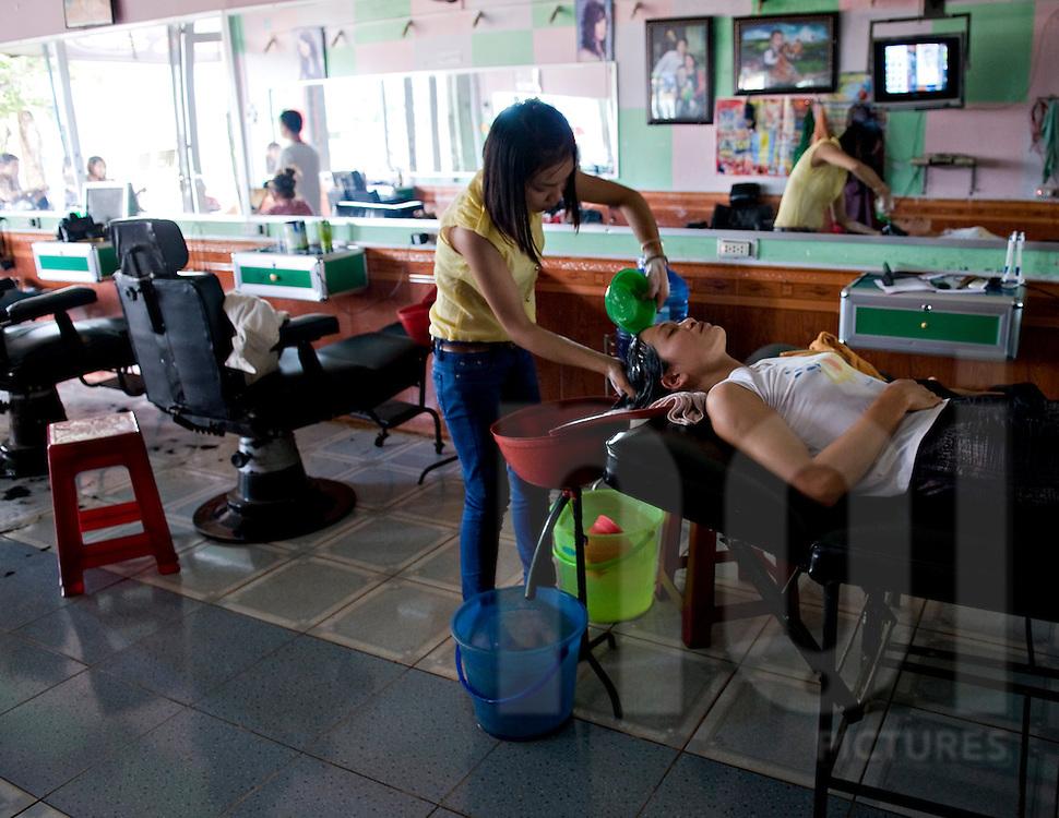 A vietnamese young woman whashes hair of a client in hair dresser shop. Pleiku area, Vietnam, Asia.