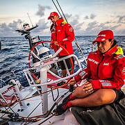 Leg 6 to Auckland, day 18 on board MAPFRE, sunrise, Rob Greenhalgh stearing and Tamara Echegoyen trimming the main sail. 23 February, 2018.