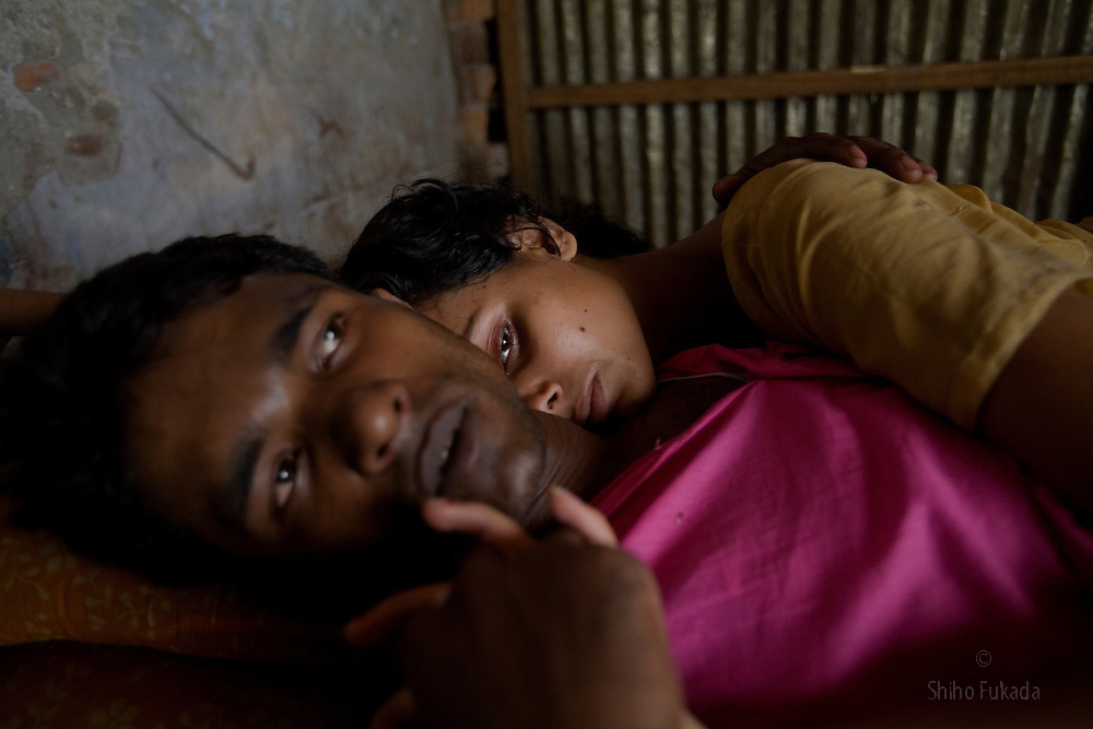Sex worker Shetu, 17, lies down with a customer at brothel in Tangail, Bangladesh.