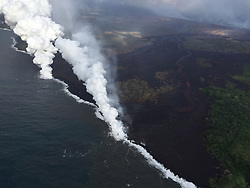 """Handout photo of KÄ«lauea Volcano — Ocean Entry. Aerial view of the active ocean entries at KÄ«lauea Volcano's lower East Rift Zone captured during this morning's HVO overflight on May 25, 2018. An ongoing hazard at the ocean entries is laze. As hot lava boils cool seawater, a series of chemical and physical reactions create a mixture of condensed acidic steam, hydrochloric acid gas, and tiny shards of volcanic glass. Blown by wind, this plume creates a noticeable downwind haze, known as """"laze"""" (short for lava haze). Laze is irritating to the lungs, eyes and skin. Photo by USGS via ABACAPRESS.COM"""