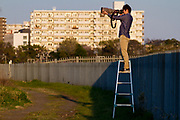 A military aircraft enthusiast uses a large camera and lens to photograph an aeroplane as it lands at Naval Air Facility, Atsugi airbase near Yamato, Kanagawa, Japan. Thursday April 4th 2019