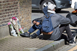 © Licensed to London News Pictures. 05/04/2018. London, UK. A man (L) who said he is the victim's brother (and did not want his face shown) sits with a friend as they view floral tributes left near a murder scene in Hackney after a 20 year old man was stabbed in Link Street. Police were approached by a man suffering from stab injuries at 8pm last night he was pronounced dead at 8. 24pm by officers. Photo credit: Peter Macdiarmid/LNP