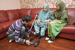 South Asian son helping his mother put on her shoes.