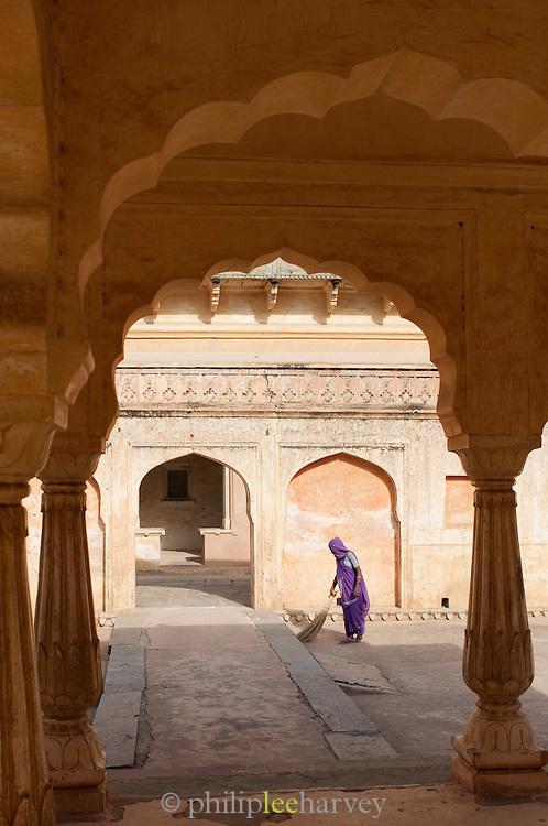 Groundswoman in sari sweeping at the Amber Fort near Jaipur, Rajasthan, India