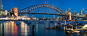 View of Sydney Harbour Bridge & Opera House from Lavender Bay. City CBD with the Sydney Tower to the right, Luna Park on the left.