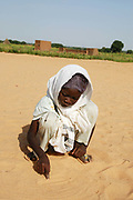 Kendrig camp for Internally Displaced People, El Geneina, West Darfur. Um Dowein school for girls. A girl writes in the sand - there are few exercise books and most lessons take place outdoors under a very hot sun.