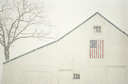 White barn with old american flag during a snow storm
