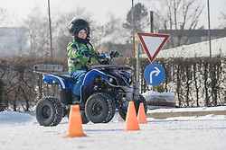 Boy riding quad bike on snow covered road