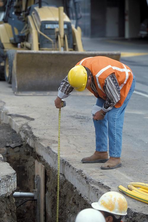 Hispanic construction worker measuring depth of hole below Colorado Street in Austin, Texas for fiber optic cables.<br /> ©Bob Daemmrich/