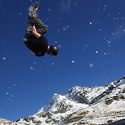 A snowboarder takes to the air at The Remarkables Ski Fields, Queenstown, New Zealand during a session with 'The Air Bag'  a large inflatable airbag which breaks the fall of the participant on landing and allows valuable experience and a training aid for Aerial skiers and snowboarders. Queenstown, South Island, New Zealand, 23rd July 2011