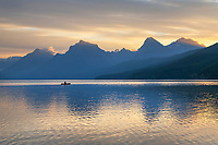 Canoeist paddling on Lake McDonald at sunrise. Glacier National Park Montana